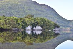Muckross Lake reflections. Reflections of hills forests and rock formations on calm surface of Muckross Lake in Ireland stock image