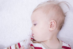 Mucus suction. Mother using nasal aspiration for infant, mucus suction Royalty Free Stock Photography