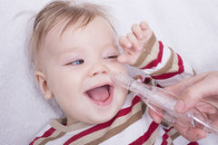 Mucus suction. Mother using nasal aspiration for infant, mucus suction Stock Photography