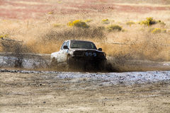 Mud Bath. A truck driving through a puddle of mud Stock Image