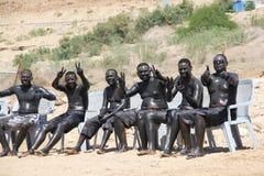 Mud bath people Stock Images