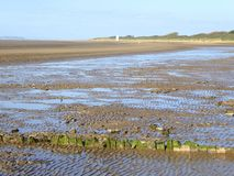 Mud beach at low tide. The mud beach and lighthouse at low tide at Burnham-on-Sea in Somerset, England royalty free stock photo