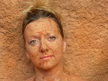 Mud Blend. Woman with facial mud blends into background Stock Photo