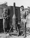 Mud covered couple with portable stove Stock Photography