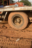 Mud Covered Truck Tire and flatbed on muddy site with Plastic bottle Stock Photos
