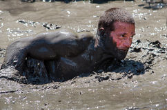 Mud crawl. A  muscular man barely holds his head above the mud as he competes in the 2012 mudathlon in Indiana Royalty Free Stock Photo