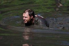 Mud crawl. A man crawls through a river of mud in the 2013 marathon called a Mudathlon, in northwest Indiana Royalty Free Stock Photos