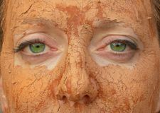 Mud Eyes. Close up of green-eyed woman with mud facial Stock Photos
