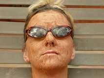 Mud Face & Glasses. Woman wears her sunglasses while getting a mud facial Stock Photography
