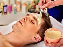 Mud facial healing mask of man in spa salon. Stock Images