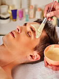 Mud facial healing mask of man in spa salon. Royalty Free Stock Photo