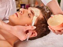 Mud facial healing mask of man in spa salon. stock photo