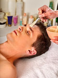 Mud facial mask of man in spa salon. Face massage . Stock Images