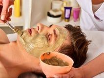 Mud facial mask of man in spa salon. Face massage. Royalty Free Stock Photos