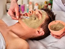 Mud facial mask of man in spa salon. Face massage . royalty free stock photo