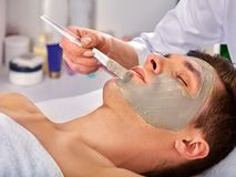 Mud facial mask of man in spa salon. Face massage . Mud facial mask of men in spa salon. Massage with clay full face in therapy room. Man lying on spa bed stock images