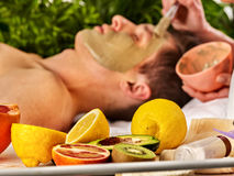 Mud facial mask of man in spa salon. Massage with clay full face. Royalty Free Stock Images