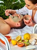 Mud facial mask of man in spa salon. Massage with clay full face. Stock Image