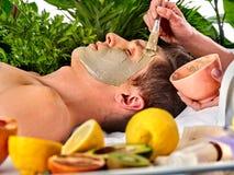 Mud facial mask of man in spa salon. Massage with clay full face. Mud facial mask of men in spa salon. Massage with clay face. Apply mask on face with brush royalty free stock photo