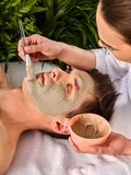 Mud facial mask of woman in spa salon. Face massage . Mud facial mask of men in spa salon. Massage with clay full face. Girl on with therapy room. Acne Removal stock image