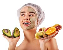 Mud facial mask of woman in spa salon. Face massage . Avocado clay face mask. Woman in medical hat holding half of green fruit on plate isolated background royalty free stock photos