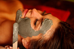 Mud facial mask of woman in spa salon. Face massage . Royalty Free Stock Image