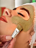 Mud facial mask of woman in spa salon. Face massage . Royalty Free Stock Images