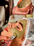 Mud facial mask of woman in spa salon. Face massage. Royalty Free Stock Photo