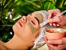 Mud facial mask of woman in spa salon. Face massage . Mud facial mask of woman in spa salon. Massage with clay full face. Girl wearing medical hat on with Stock Photo