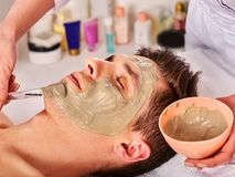 Mud facial mask of woman in spa salon. Face massage . Mud facial mask of man in spa salon. Cleansing massage with clay full face. Lying man on therapy room for royalty free stock photo