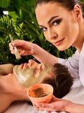Mud facial mask of woman in spa salon. Face massage . Stock Photos