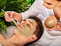 Mud facial mask of woman in spa salon. Face massage . Royalty Free Stock Photo