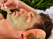 Mud facial mask of woman in spa salon. Face massage . Mud facial mask of man in spa salon. Massage with clay full face. Girl on with therapy room. Man lying Royalty Free Stock Photo