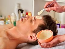Mud facial mask of woman in spa salon. Face massage . Stock Photography