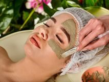 Mud facial mask of woman in spa salon. Face massage . Mud facial mask of woman in spa salon. Massage with clay full face. Girl wearing medical hat on with Stock Photography
