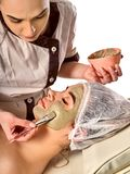 Mud facial mask of woman in spa salon. Face massage . Mud facial mask of women in spa salon. Massage with clay full face mud from dead sea . Girl on with stock photos