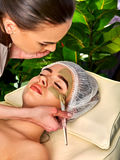 Mud facial mask of woman in spa salon. Face massage . Mud facial mask of women in spa salon. Massage with clay full face. Girl wearing medical hat on with Royalty Free Stock Photo