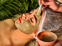 Mud facial mask of woman in spa salon. Face procedure . Stock Photography