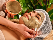 Mud facial mask of woman in spa salon. Face procedure . Royalty Free Stock Image