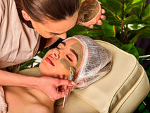 Mud facial mask of woman in spa salon. Face procedure . Royalty Free Stock Images