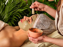 Mud facial mask of woman in spa salon. Face procedure . Royalty Free Stock Photos