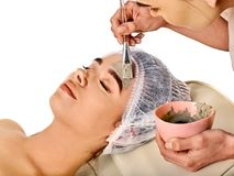 Mud facial mask of woman in spa salon. Face massage. Mud facial mask of woman in spa salon. Massage with clay full face. Girl on with therapy room. Beautician stock photography