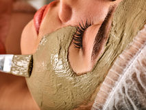 Mud facial mask of woman in spa salon. Massage with clay full face. Girl on with therapy room. Beautician with brush therapeutic procedure. Mask made of Stock Image