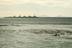 Mud flat and people with factory silhouette Stock Photo