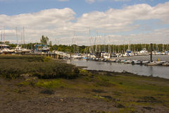 The mud flats at Bucklers hard on the Beaulieu River in Hampshire, England at low tide with boats on their moorings Stock Photos