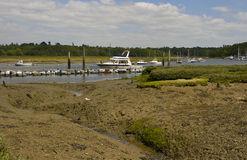 The mud flats at Bucklers hard on the Beaulieu River in Hampshire, England at low tide with boats on their moorings Royalty Free Stock Photo