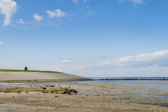 Mud-flats and Dike of Waddensea and Church Royalty Free Stock Images