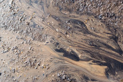 Mud Flow Stains. Water washes mud and grime to create natural patterns on the surface of a sand and stone based background Royalty Free Stock Image