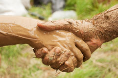 Mud handshake. Handshake of dirty mud hands on grass background royalty free stock photo