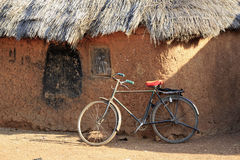 Mud huts and bike. In a traditional African village Royalty Free Stock Image